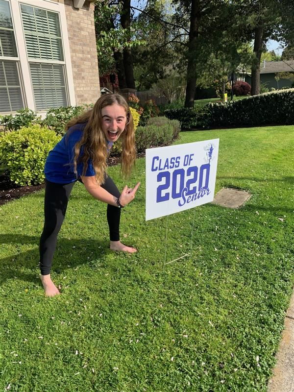 Students celebrate their new yard signs.