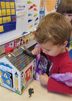 Student using fine motor skills while using a key to open a toy house.