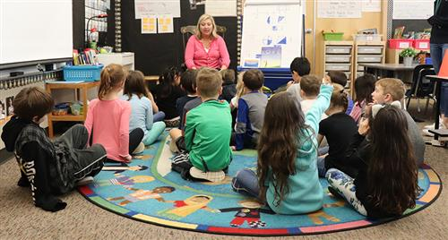 Boones Ferry Primary Counselor Katie Flaker reads a book to first-graders.